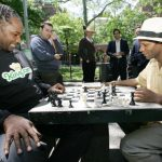 """New York, UNITED STATES: British boxer Lennox Lewis (L) plays chess against Poe McClinton in Washington Square Park 23 May 2006 in New York. Lewis appeared to promote his participation in an online chess competition. McClinton, when asked about Lewis' ability to play chess said, """"He's not bad for a boxer."""" AFP PHOTO/Don EMMERT (Photo credit should read DON EMMERT/AFP/Getty Images)"""